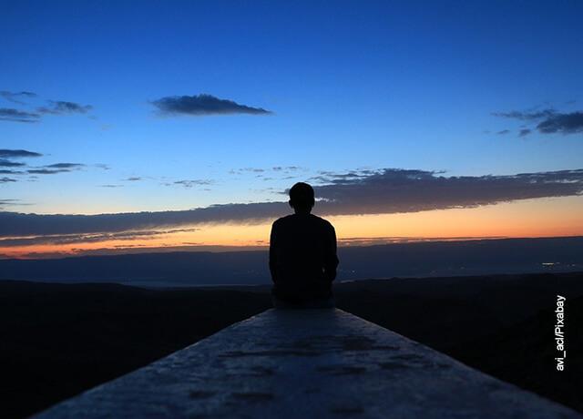 Foto de una persona sentada en el borde de una montaña que ilustra cómo hacer un objetivo