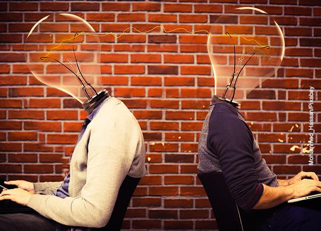 Foto de dos personas con cabeza de bombillo sentadas