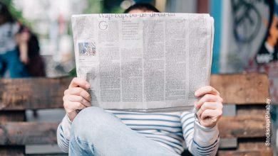 Foto de un hombre sentado leyendo un periódico