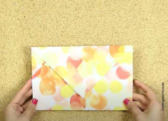 Foto de unas manos sosteniendo un papel plegado que muestra cómo hacer un sobre de carta