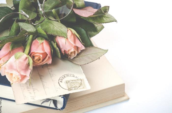 Foto de una carta con unos libros y unas rosas