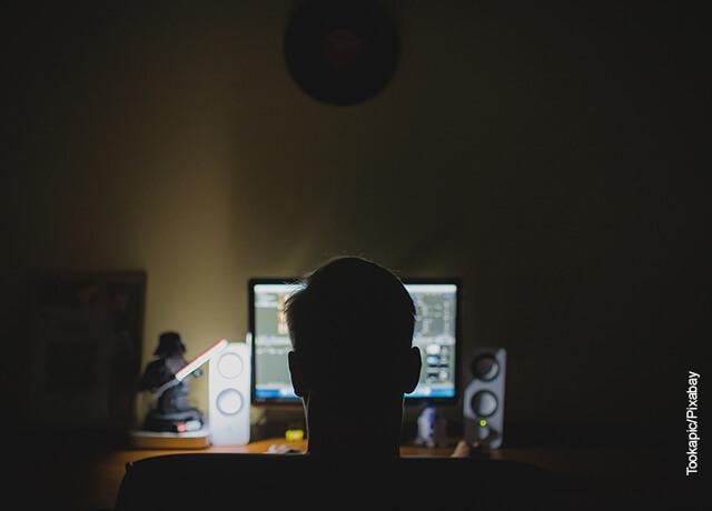 Foto de un hombre sentado frente a su computador trabajando que muestra cómo hacer una portada con normas APA
