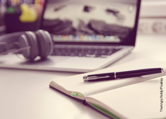 Foto de un bolígrafo y una libreta sobre una mesa