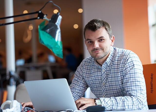 Foto de un hombre sonriendo sentado frente a su computador