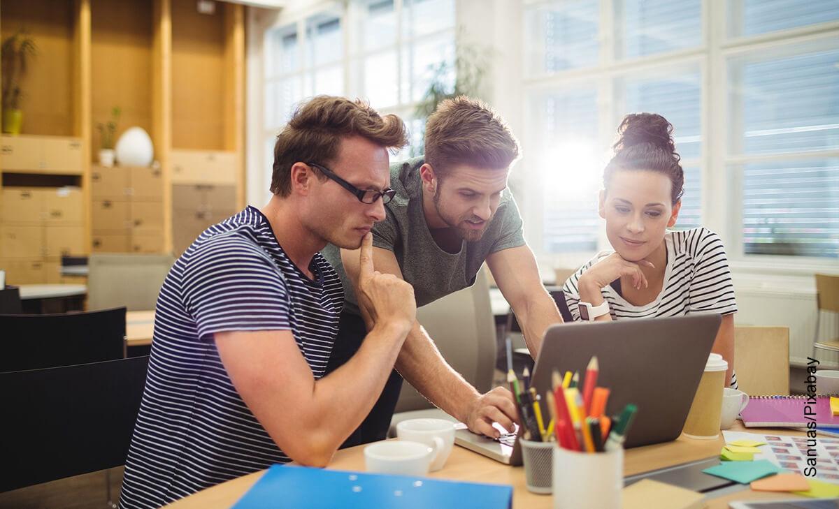 Foto de tres jóvenes sentados frente al computador que muestra cómo hacer una portada con normas APA