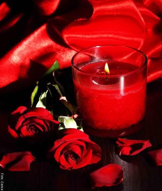 Foto de una vela roja rodeada de rosas
