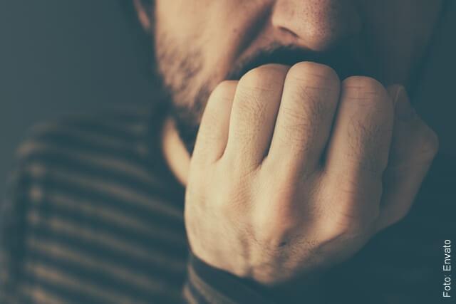 foto que ilustra un hombre angustiado mordiendo sus uñas