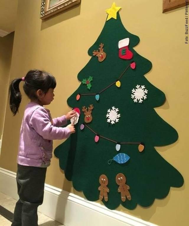 Foto de una niña adornando un arbolito navideño hecho en foami