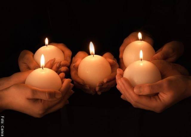 Foto de velas encendidas sostenidas por varias manos