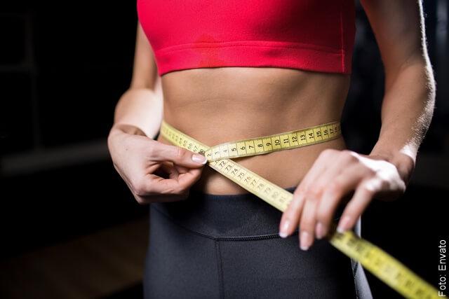 foto que ilustra la pérdida de peso en una mujer con un metro en su cintura