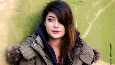 Foto de una mujer sonriente frente a una pared
