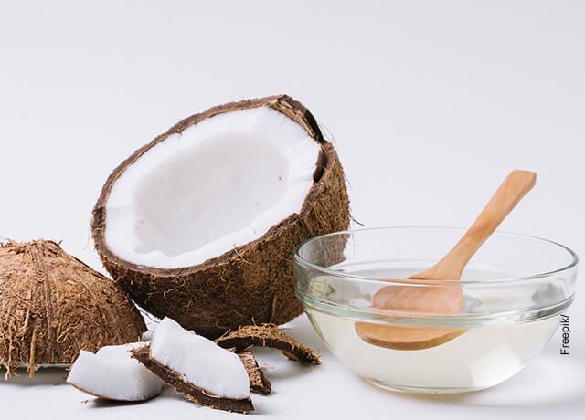 Foto de un coco junto con su aceite sobre una mesa