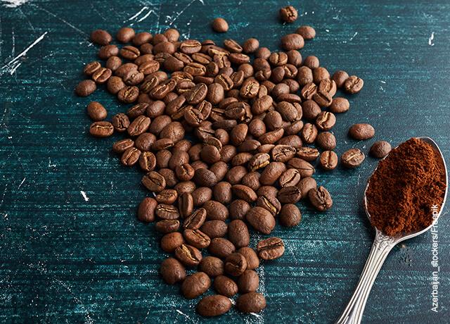 Foto de granos de café y café molido sobre una mesa azul
