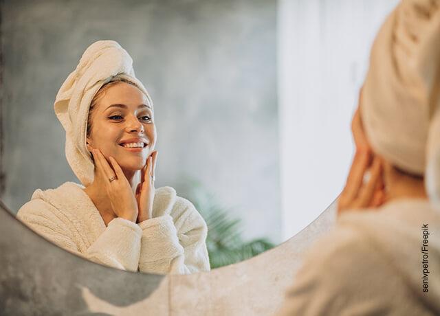 Foto de una mujer sonriente recién bañada frente al espejo