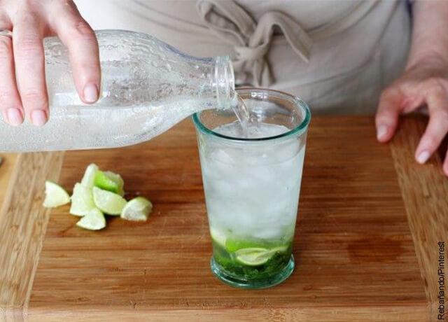 Foto de una persona sirviendo soda en un vaso con limón y hierbabuena