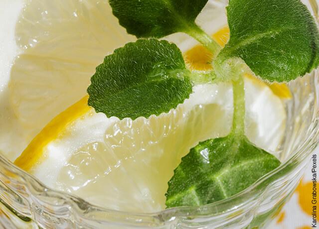Foto de vaso con hielo, limón y hojas de hierbabuena que muestra los mojitos y su receta