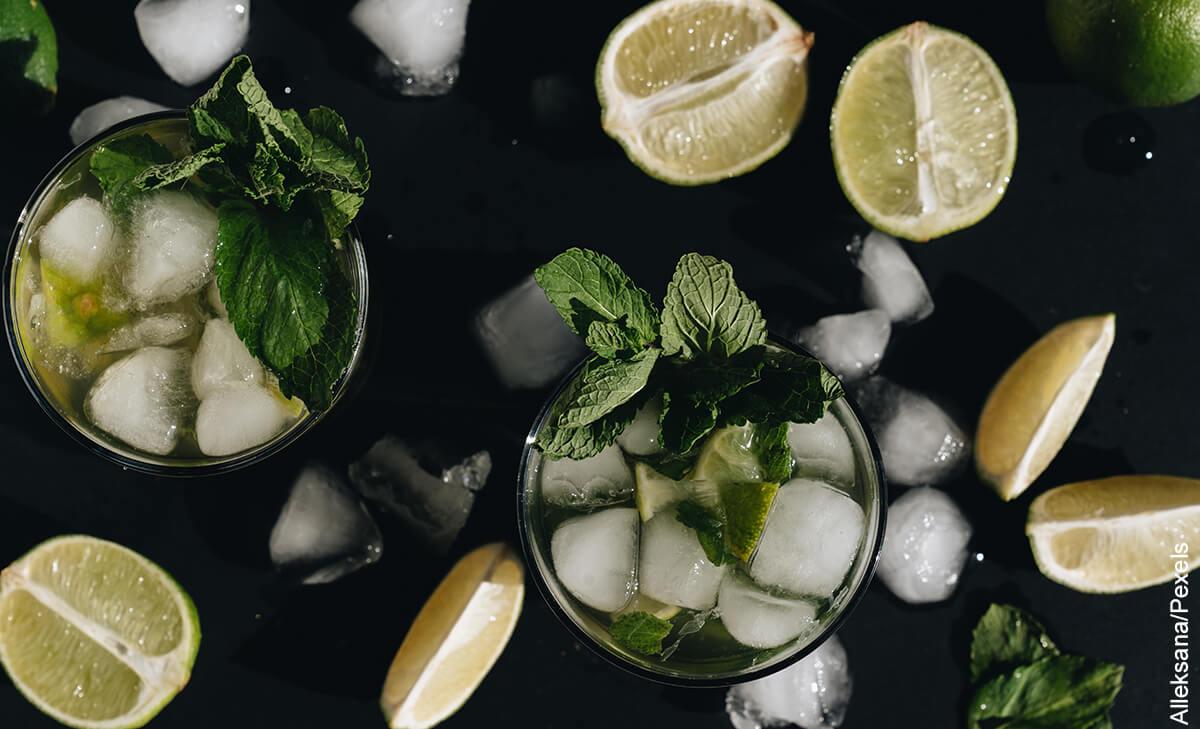 Foto de dos vasos sobre una mesa con trozos de limón, hielo y hierbabuena que muestra los mojitos y su receta