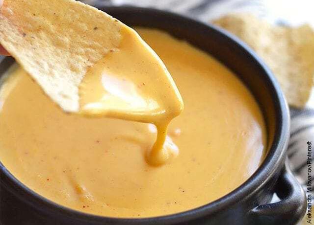 Foto de un nacho untado con salsa de queso cheddar