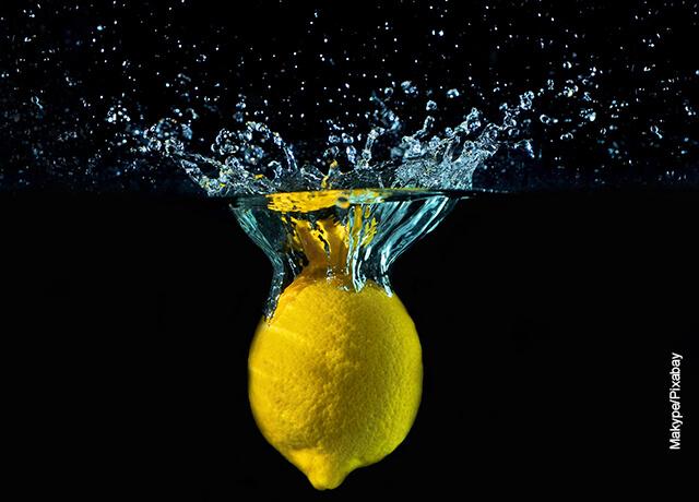 Foto de un limón entero cayendo sobre el agua