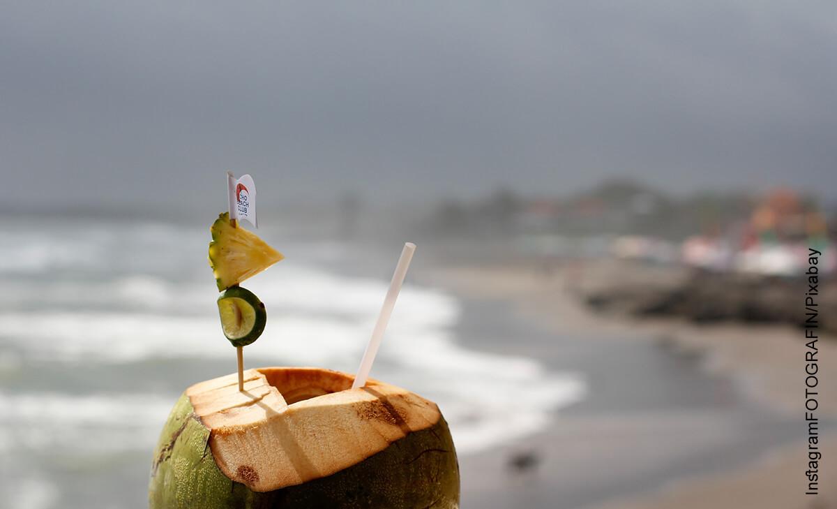 Foto de una bebida exótica en la playa que muestra para qué sirve el agua de coco