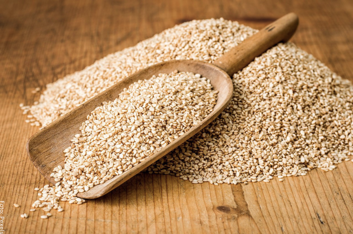 Foto de una cuchara de madera con varias semillas de ajonjolí