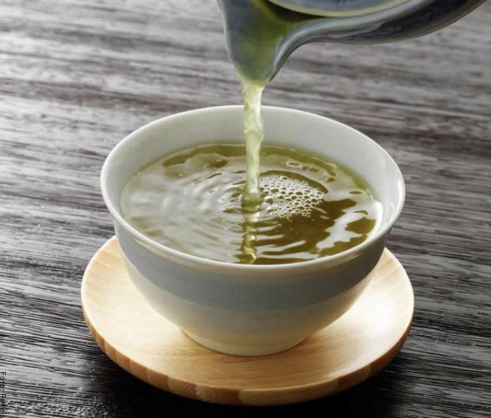 Foto de una persona sirviendo té de cilantro en una taza