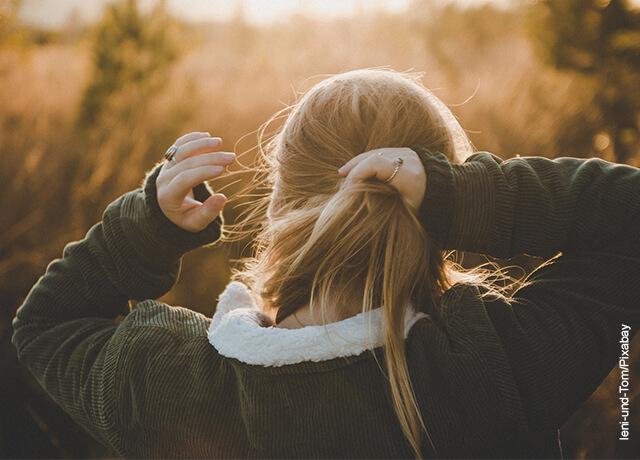 Foto de una mujer haciéndose una cola de caballo en el pelo