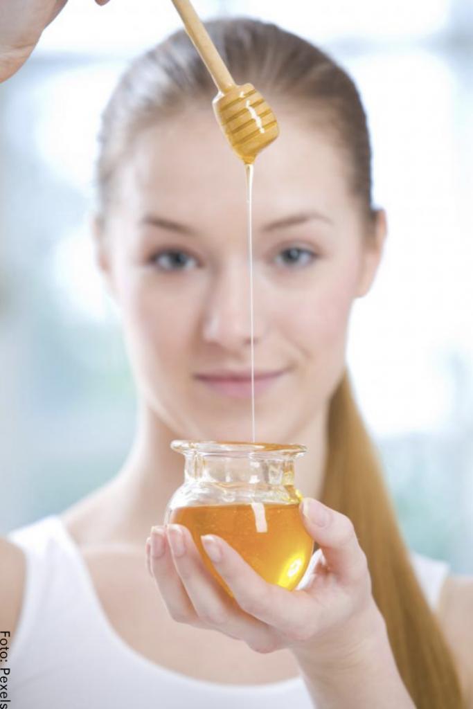 Foto de una mujer sosteniendo un frasco de miel