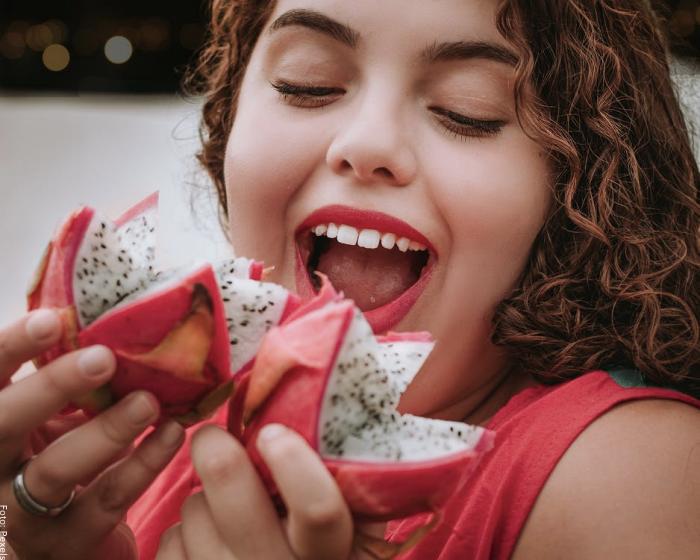 Foto de una mujer comiendo pitahaya
