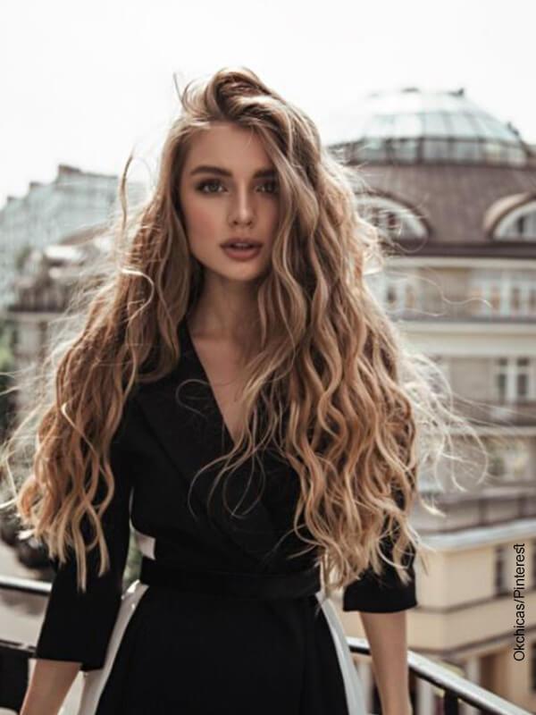 Foto de una mujer de melena rizada que ilustra peinados para cabello largo
