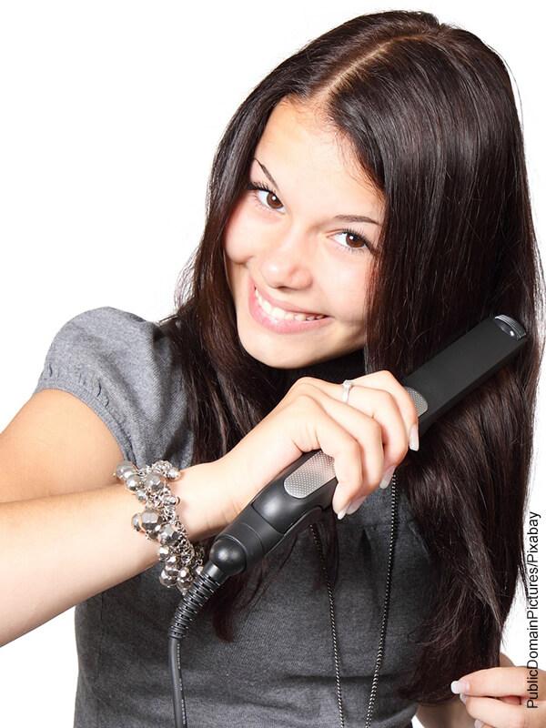 Foto de una mujer alisando su cabello con una plancha de pelo