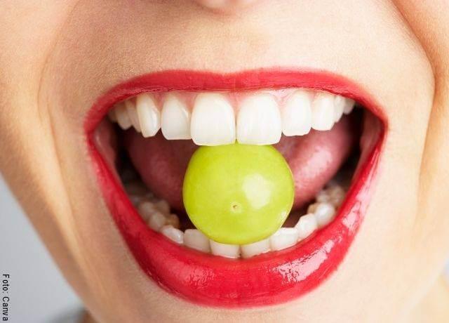 Foto de una uva en la boca de una mujer