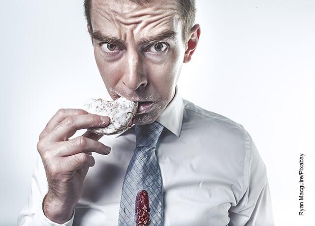 Foto de un hombre comiendo una galleta