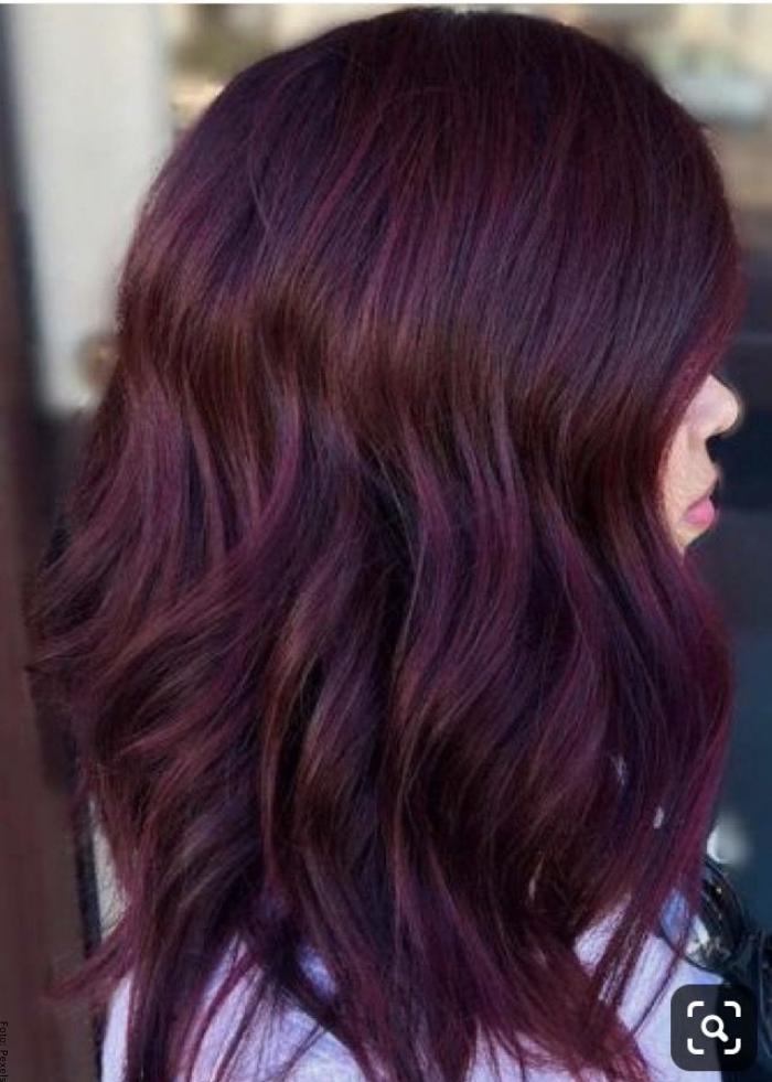Foto de una mujer con cabello rojo vino con matices violetas