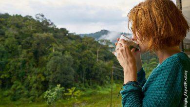 Foto de una mujer bebiendo de una taza al aire libre que ilustra el carbonato de calcio para qué sirve