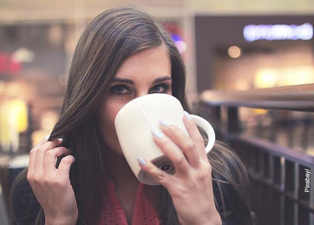 Foto de una mujer bebiendo de una taza que ilustra el carbonato de calcio para qué sirve