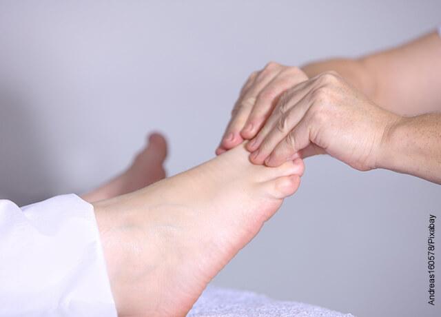 Foto de una mano masajeando el pie de alguien