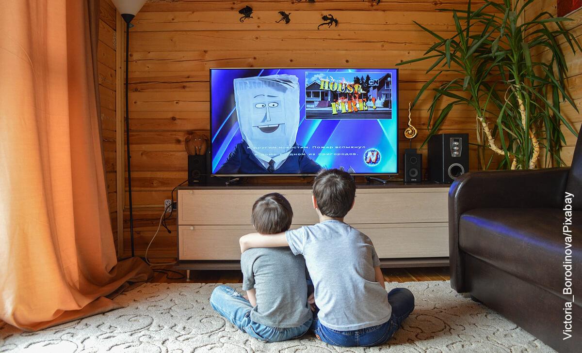 Foto de dos niños abrazados viendo televisión que muestra las caricaturas de los 90