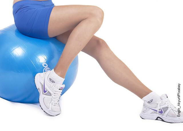 Foto de una mujer sentada sobre un balón de pialtes que muestra cómo adelgazar las piernas