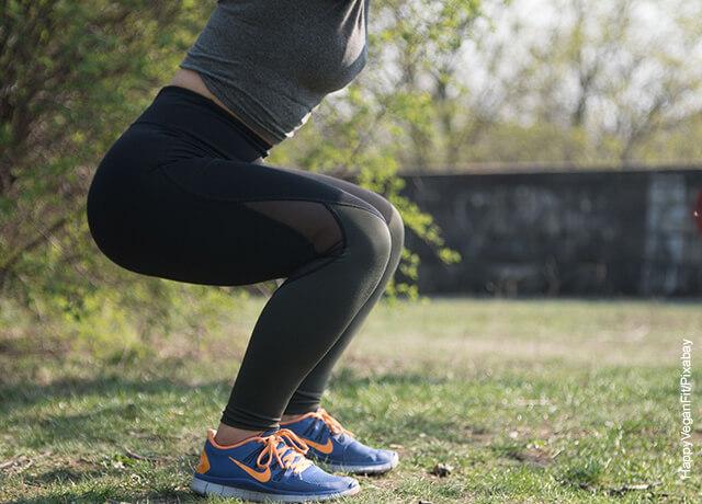 Foto de una mujer haciendo sentadillas que ilustra cómo adelgazar las piernas
