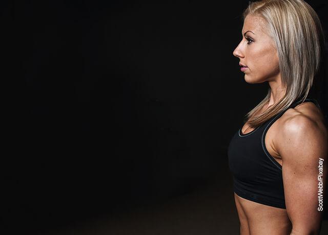Foto de una mujer mostrando sus brazos en el gimnasio