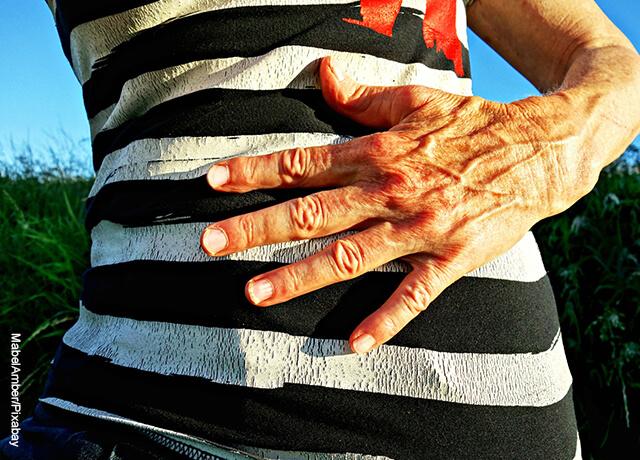Foto de una mujer adulta mayor tomándose el abdomen