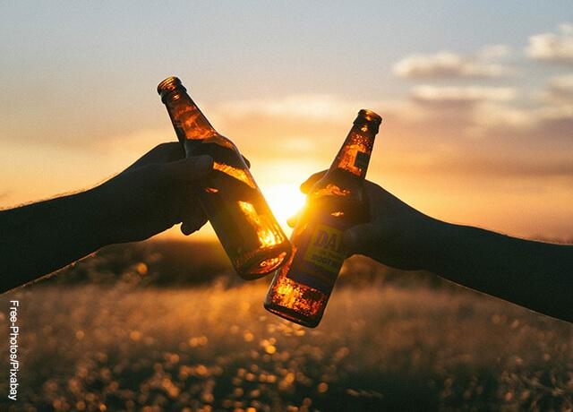 Foto de dos manos brindando con cerveza al aire libre que ilustra cómo desintoxicar el hígado