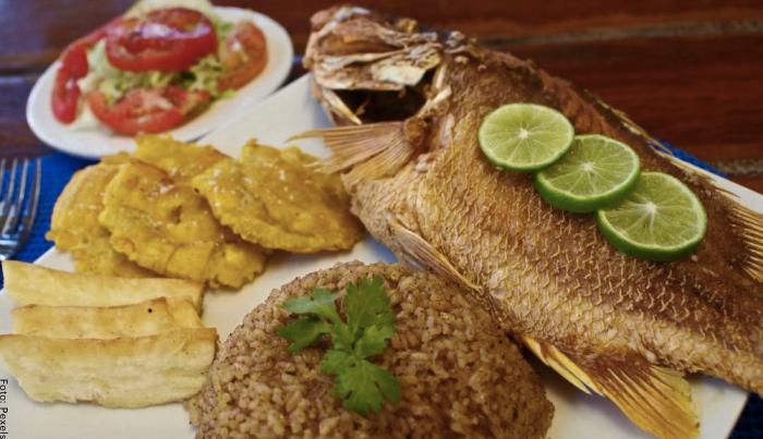 Foto de un plato de arroz con coco, pescado y patacones