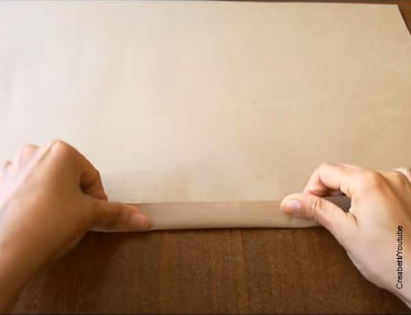 Foto de unas manos doblando papel que muestran cómo hacer bolsas de papel