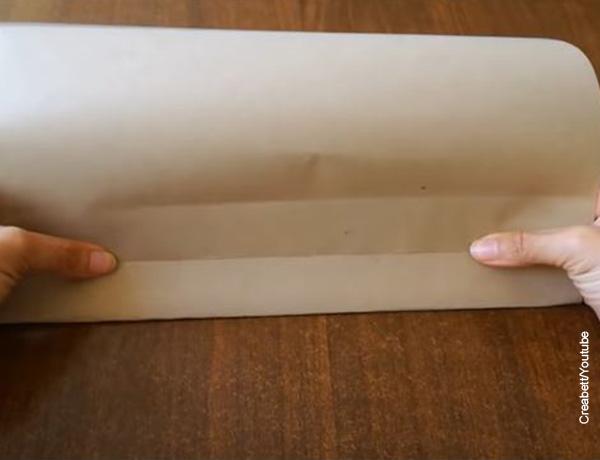 Foto de unas manos realizando un pliegue sobre una hoja que ilustra cómo hacer bolsas de papel