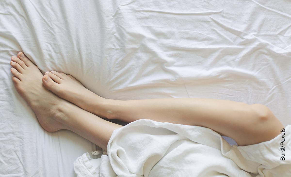 Foto de las piernas de una mujer sobre su cama que muestra cómo hacer cera casera