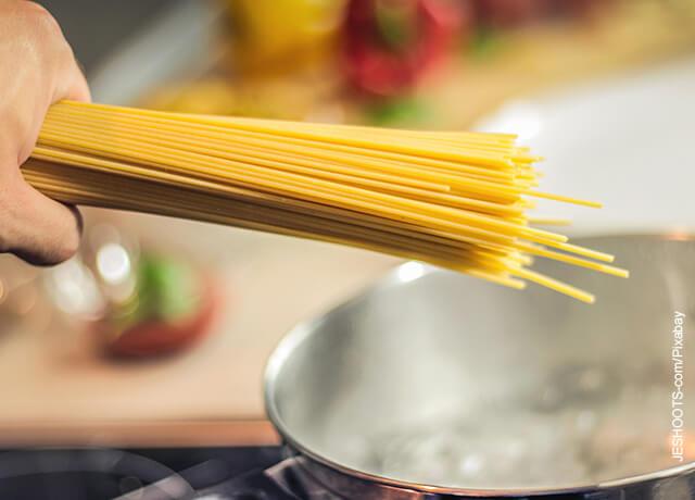 Foto de una mano sosteniendo pasta cruda que ilustra cómo hacer espagueti