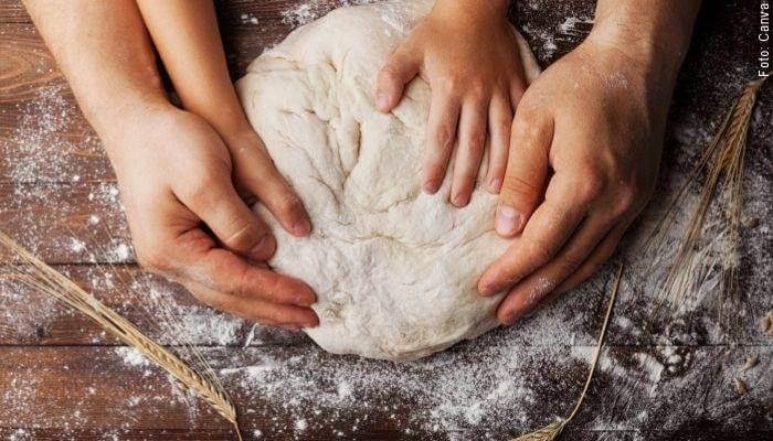 Foto de las manos de un adulto y un niño amasando masa