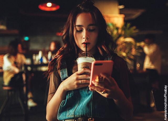 Foto de una mujer tomando un café y mirando su celular